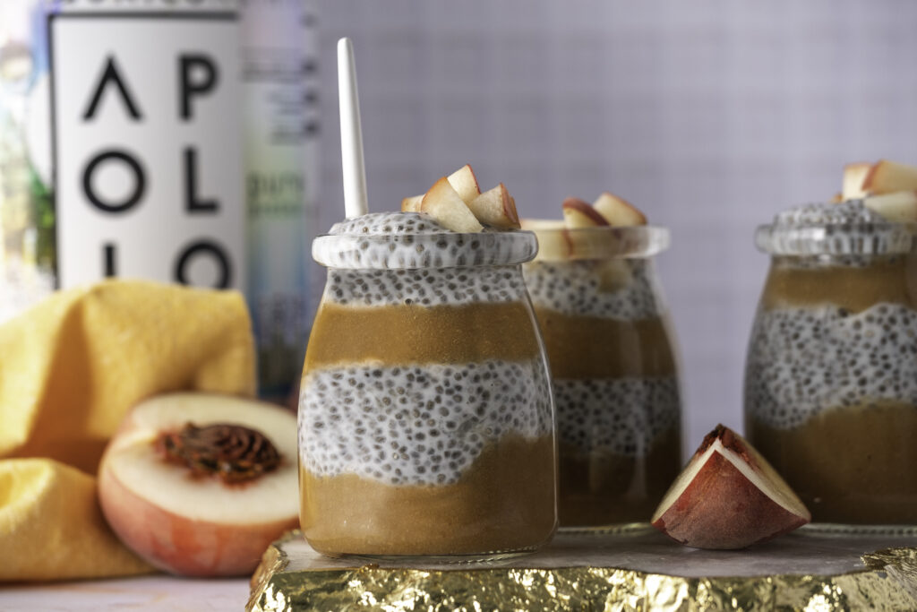 peach chia protein in mason jar with fresh sliced peaches, and jar of vanilla protein powder in background
