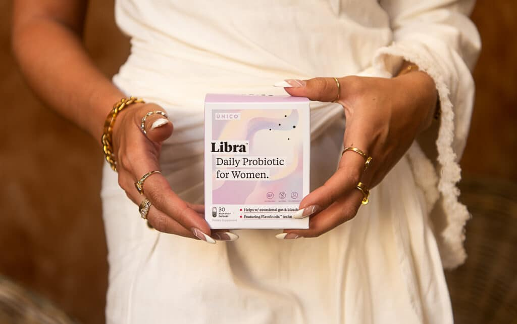 woman's hands holding a probiotic supplement for maintaining optimal gut health
