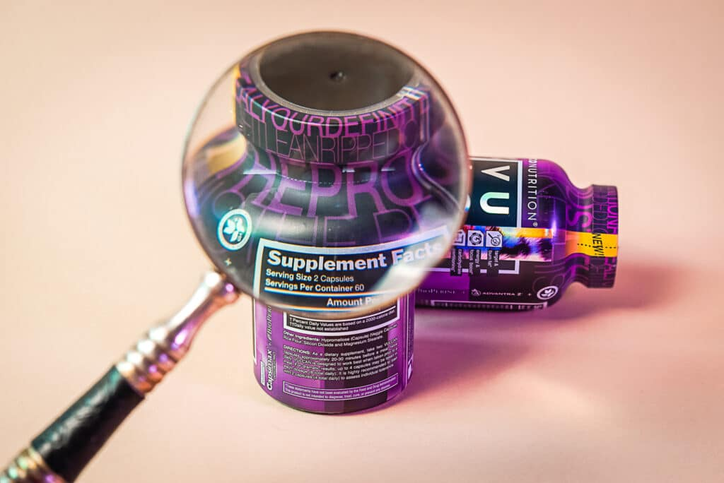 weight loss product with magnifying glass showing close-up of supplement facts panel. Tan background